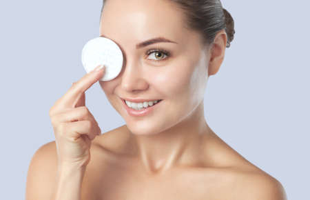 Beautiful smiling woman with clean skin holds a cotton pad. Womens cosmetology, skin care. Stok Fotoğraf