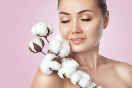 Portrait of a beautiful woman with beautiful make-up, with cotton flower in her hand on a pink background. Cosmetology and professional skin care.