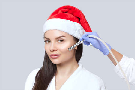 Cosmetologist does the procedure Microdermabrasion on the face of a beautiful woman in a Santa Claus hat. New Years and Cosmetology concept. Stockfoto