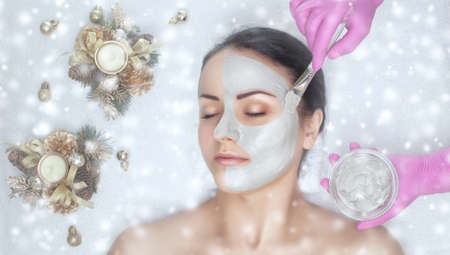 A doctor does face mask the skin to beautiful woman. Next to her are Christmas decorations. There are snowflakes in the background. New Year's and Cosmetology concept.