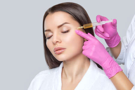 Cosmetologist does prp therapy on the face of a beautiful woman with clean skin in a beauty salon. There is in vitro blood plasma, ready for injection. Cosmetology concept.