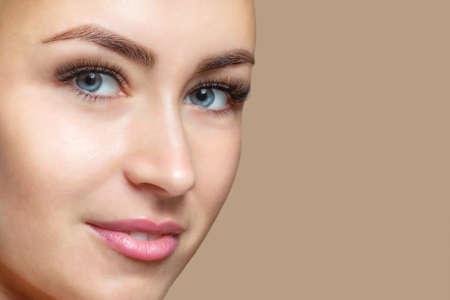 파란 눈을 가진 깨끗한 피부를 가진 아름다운 행복한 웃는 여성의 초상화. 전문 메이크업 및 미용 피부 관리.