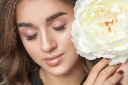 Portrait of a beautiful happy woman with clean skin and beautiful nude make-up. Beautiful eyes close up. She holds a white peony near her face.Cosmetology skin care and make-up concept