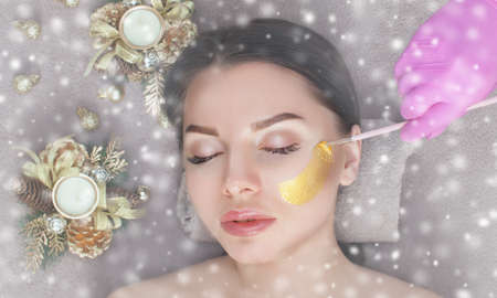 Beautician makes a golden mask to rejuvenate the skin to beautiful woman. Next to her are Christmas decorations.New Years and Cosmetology concept. 版權商用圖片