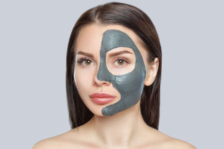 Beautician makes a mud mask to cleanse the skin and anti-wrinkle on the face of a beautiful woman, spa treatments and cosmetology concept.