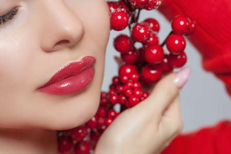Portrait of a beautiful sensual brunette woman with nude make-up in a red sweater holding red Christmas decorations near her face. New Year and cosmetology concept.
