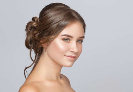 Portrait of a beautiful sensual light brown haired woman with a wedding hairstyle and nude make-up in a beauty salon.Wedding hairstyle and makeup concept 版權商用圖片