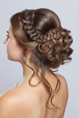Retrato de una bella mujer sensual de cabello castaño claro con un peinado de novia y maquillaje en un salón de belleza. Peinado de boda.