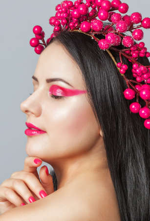 Portrait of a beautiful happy woman with beautiful creative makeup in pink colors and pink manicure. She has a wreath of berries on her head. New Years concept and make-up.