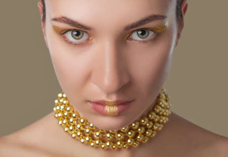 Portrait of a beautiful happy woman with beautiful creative makeup in gold colors. She has gold beads on her neck. Make-up concept. 版權商用圖片