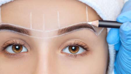 Makijaż permanentny brwi pięknej kobiety o gęstych brwiach w gabinecie kosmetycznym. Kosmetyczka zbliżenie robi tatuażu brwi. Zbliżenie twarzy. Koncepcja makijażu i kosmetologii.
