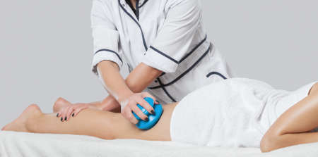 A masseur makes anti-cellulite massage on the legs, thighs, hips and buttocks with a vacuum massager in the spa. Overweight treatment, body sculpting.Cosmetology and massage concept.