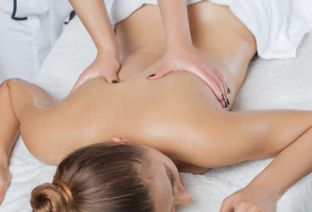 Masseur makes a relaxing massage on the neck, shoulders, back and collarbones of a young beautiful woman in a spa. Cosmetology and massage concept.