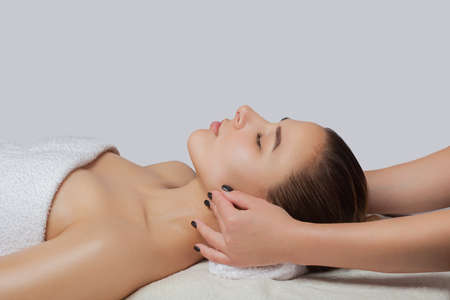 Masseur makes a relaxing massage on the ears, face, neck, shoulders and collarbones of a young beautiful woman in a spa. Cosmetology and massage concept.