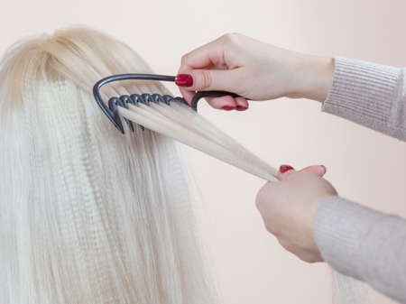 Hairdresser is combing her long hair of beautiful blonde woman in the beauty salon. Professional hair care and creating hairstyles.