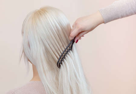 Hairdresser is combing her long hair of beautiful blonde woman in the beauty salon. Professional hair care and creating hairstyles. 版權商用圖片 - 136973374