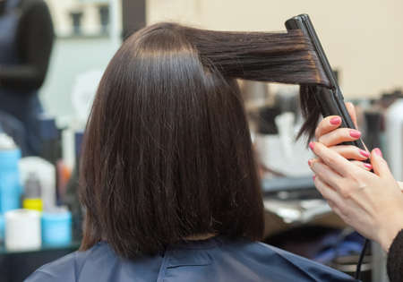 The hairdresser does aligns the hair with hair iron to a young girl, brunette in a beauty salon. Professional Hair Care 版權商用圖片