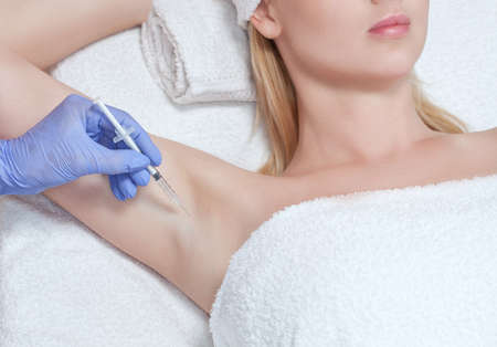 The doctor makes injections of botulinum toxin in the underarm area against hyperhidrosis. Treatment of problem skin cosmetology concept.
