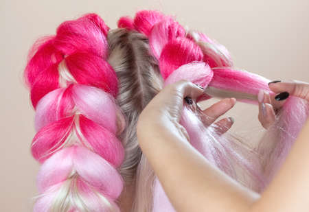 The hairdresser weaves braids with pink kanekalons beautiful blonde beauty salon.Beautiful hairstyles.