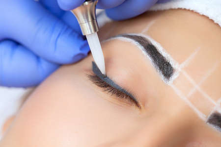Permanent make-up for eyebrows of beautiful woman with thick brows in beauty salon. Closeup beautician doing  tattooing eyebrow. Face close-up. Make-up and Cosmetology concept. 版權商用圖片