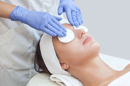 Beautician cleanses the skin on the face from acne and blackheads on the womans face in a beauty salon.Treatment of problem skin cosmetology concept.