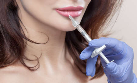 Cosmetologist does prp therapy anti wrinkle and aging skin on the chin and on the face of a beautiful woman in a beauty salon. Cosmetology concept. Zdjęcie Seryjne