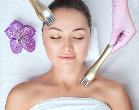 The cosmetologist does rf-lifting of the face skin of a beautiful woman in a beauty salon. Rf lifting procedure in a beauty salon. Cosmetology and professional skin care.
