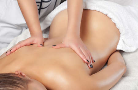 Masseur makes a relaxing massage on the neck, shoulders and  back of a young beautiful woman in a spa. Cosmetology and massage concept. 版權商用圖片