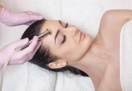 The cosmetologist makes the procedure Microdermabrasion of the face skin of a beautiful woman in a beauty salon.Cosmetology and professional skin care.