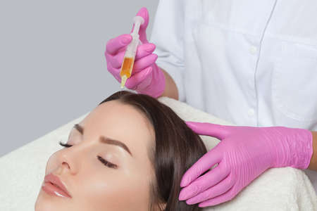 Cosmetologist does prp therapy against hair loss and anti-dandruff of a beautiful woman in a beauty salon. Cosmetology concept.