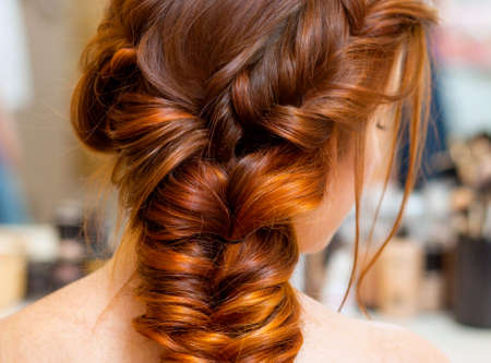 Beautiful woman with long red hair at the beauty salon, hairdresser braided a braid in a beauty salon. Professional hair care and creating hairstyles.