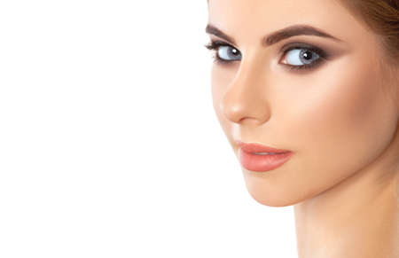 Beautiful woman with long eyelashes, beautiful make-up and thick eyebrows. Beautiful grey eyes close up. Looking at the camera. Professional makeup and cosmetology skin care.
