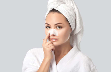 Portrait of a beautiful woman with clean skin after shower, with nose strips for blackhead removal. Cosmetology and skin care.