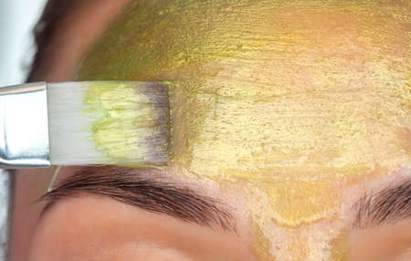 Beautician makes a face mask with gold particles on the forehead of a woman to rejuvenate the skin. Cosmetology treatment of problem skin on the face and body.