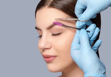 Makeup artist comb and trim the eyebrows with scissorss to a woman before staining with henna. Women's cosmetology in the beauty salon.