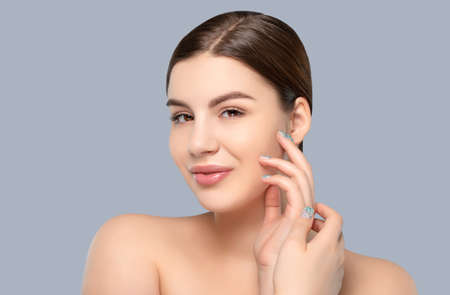 Portrait of a beautiful happy woman with a beautiful smile, clean and healthy skin and nude makeup on a blue background. Cosmetology skin care and makeup.