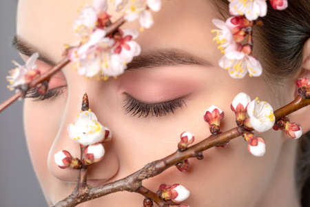 Young girl with beautiful nude make-up, thick eyebrows. Beautiful hazel eyes close up. Near her are beautiful blooming spring sakura flowers. Looking at the camera. Professional makeup and cosmetology 写真素材