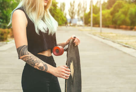 A beautiful, sexy hipster blonde woman with blue hair in tattoo stands with a longboard  on the street.Longboard riding and sport concept.