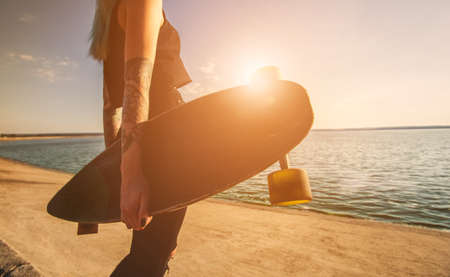 A beautiful, sexy hipster girl in tattoos stands with a longboard against the sunset at the sea. Longboard riding and sport concept.
