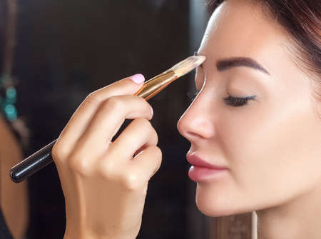 Portrait of a beautiful happy woman with clean skin in a beauty salon. Makeup artist does make-up to her. Professional makeup and cosmetology skin care.