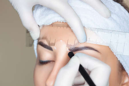 Permanent make-up for eyebrows of beautiful woman with thick brows in beauty salon. Closeup beautician doing tattooing eyebrow. Professional makeup and cosmetology skin care. 写真素材