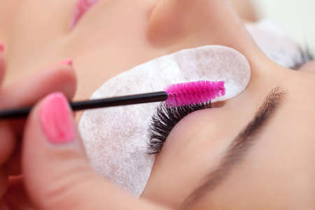 Eyelash extension procedure close up. Beautiful woman with long eyelashes in a beauty salon. Women's cosmetology in the beauty salon. Makeup concept