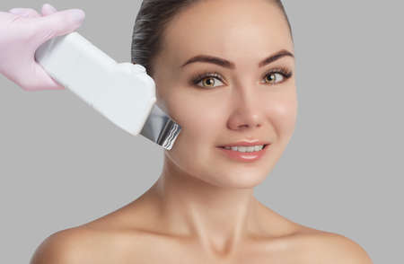 The doctor-cosmetologist makes the apparatus ultrasound cleaning procedure of of the facial skin of a beautiful young woman in a beauty salon. Cosmetology and professional skin care. 写真素材