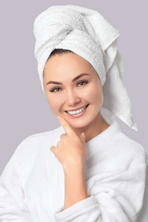 Portrait of a beautiful, smiling woman with clean skin in a white bathrobe and with a towel on her head after taking a shower. Cosmetology and skin care.