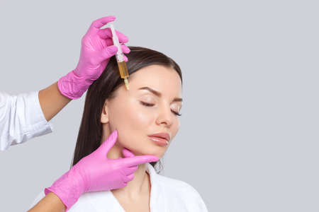 Cosmetologist does prp therapy anti wrinkle and aging skin on the face of a beautiful woman in a beauty salon. Cosmetology concept. 写真素材