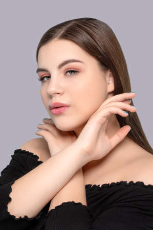 Portrait of a beautiful girl with a beautiful clean skin and nude pink makeup on a blue background. Cosmetology skin care and makeup.
