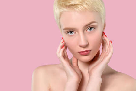 Portrait of a beautiful woman with short blonde hair, beautiful fresh make-up and with healthy clean skin on a pink background. Make-up and cosmetology concept. Imagens