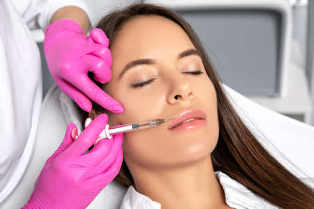 Woman with beautiful clean skin. Cosmetologist does injections for lips augmentation and anti wrinkle of a beautiful woman. Women's cosmetology in the beauty salon.
