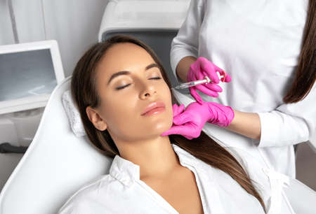 Beautiful brunette woman at the beautician.Cosmetologist does anti wrinkle injections on the face and on cheekbone. Women's cosmetology in the beauty salon.