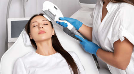 Elos epilation hair removal procedure on the face of a woman. Beautician doing laser rejuvenation on the forehead in a beauty salon. Facial skin care. Hardware ipl cosmetology